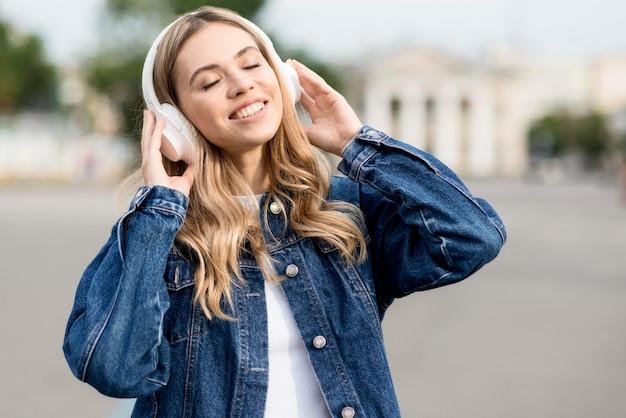 Ragazza bionda carina che ascolta la musica