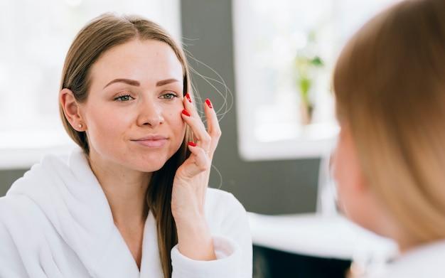 Ragazza bionda che applica la crema sul viso