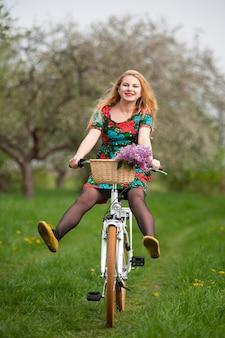 Ragazza bionda che guida una bicicletta dell'annata con le gambe di sollevamento