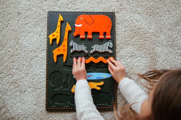 Ragazza bionda che impara con un puzzle a casa