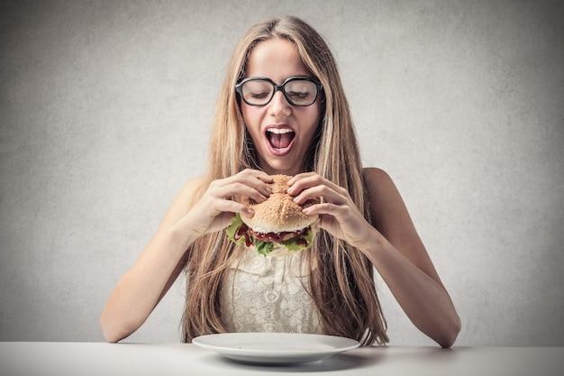 Ragazza bionda che mangia un hamburger