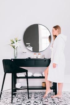 Ragazza bionda che posa nel bagno con accappatoio