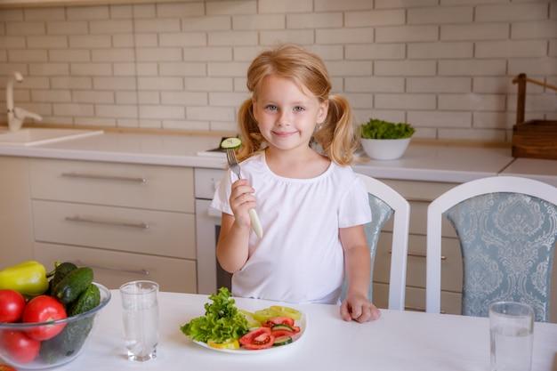 Ragazza bionda che si siede al tavolo in cucina a mangiare verdure