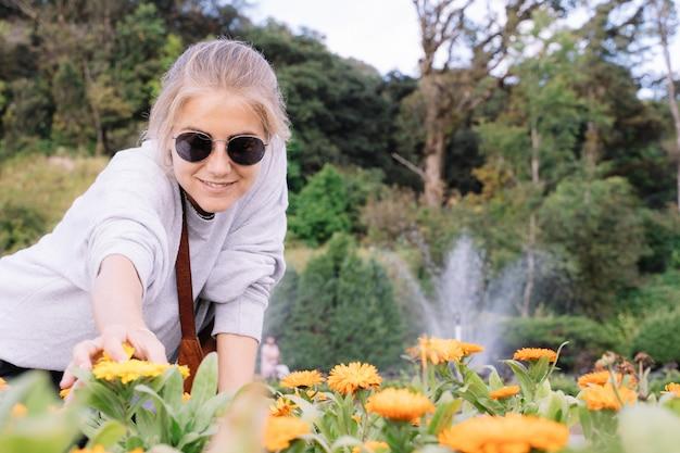 Ragazza bionda che sorride con gli occhiali da sole che tengono alcuni garofani gialli con un getto di acqua che esce