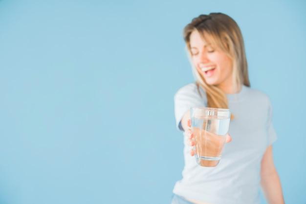 Ragazza bionda che tiene bicchiere d'acqua