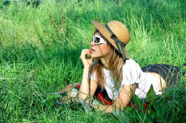 Ragazza bionda con cappello e occhiali da sole posa sul campo in erba