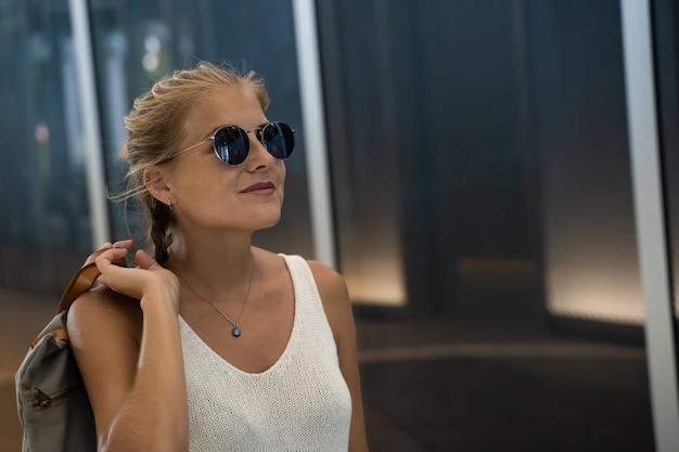 Ragazza bionda con gli occhiali da sole e una canottiera bianca che tiene una borsa con la mano sulla schiena in piedi davanti a un edificio moderno