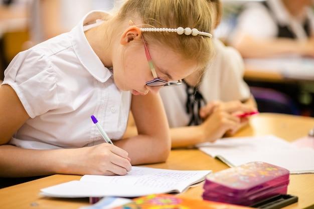 Ragazza bionda con grandi occhiali seduto in aula, studiando, sorridendo. istruzione sulla scuola elementare, primo giorno a scuola