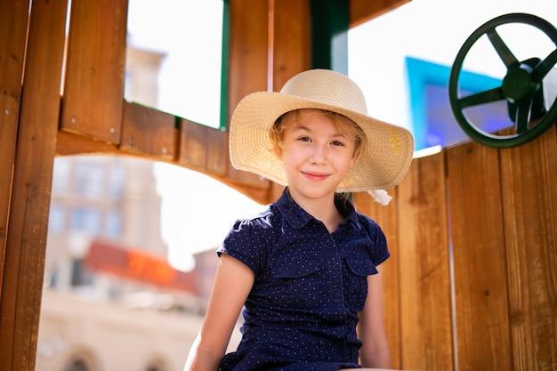 Ragazza bionda con il cappello nella casa di legno nel parco giochi per bambini