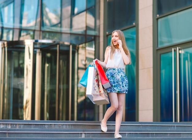 Ragazza bionda, con le borse della spesa che esce dal negozio e parla al telefono cellulare.