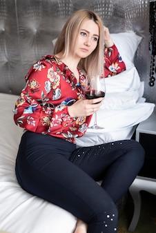 Ragazza bionda con un bicchiere di vino che osserva via