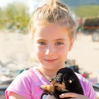 Ragazza bionda del bambino che gioca con sorridere del cucciolo di cane