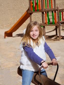Ragazza bionda del bambino che gioca nel campo da giuoco che sorride sull'oscillazione