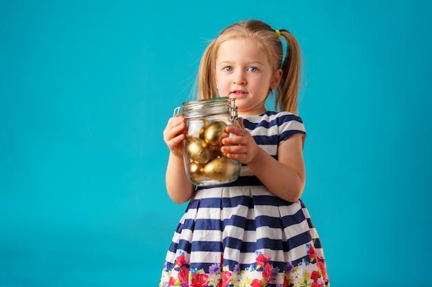 Ragazza bionda del bambino con il barattolo di vetro pieno di uova dipinte dorate per pasqua