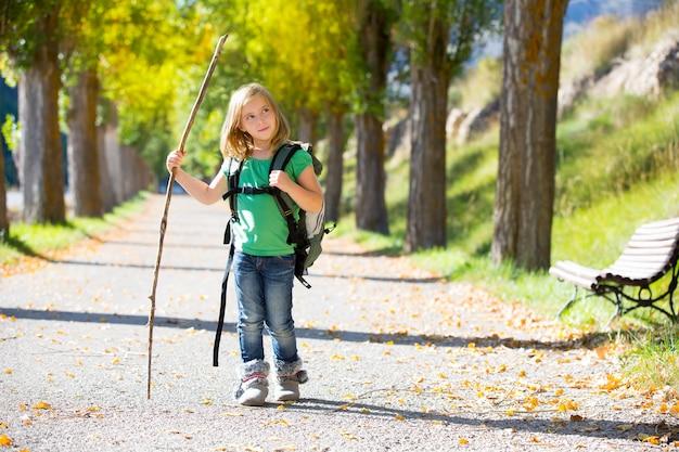 Ragazza bionda del bambino dell'esploratore che cammina con lo zaino negli alberi di autunno