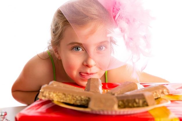 Ragazza bionda del bambino di gesto affamato in cioccolato del partito
