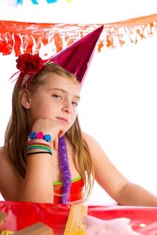 Ragazza bionda del bambino di gesto annoiato in cappello di compleanno del partito