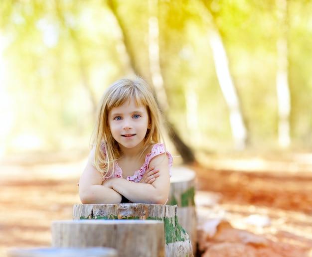 Ragazza bionda del bambino nella foresta del tronco d'albero