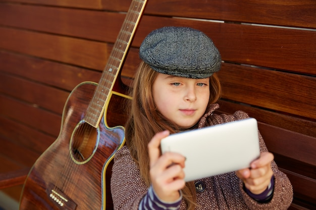 Ragazza bionda del bambino prendendo selfie chitarra e berretto invernale