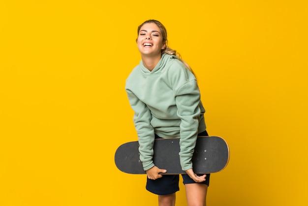 Ragazza bionda del pattinatore dell'adolescente sopra giallo isolato
