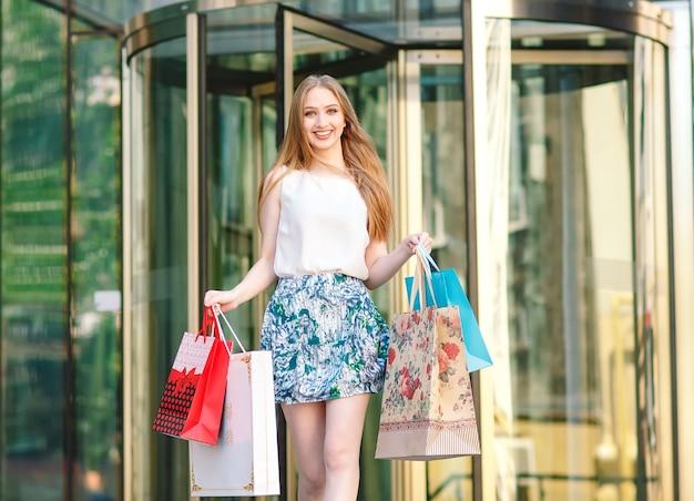 Ragazza bionda del ritratto di stile di vita giovane, con i sacchetti della spesa che cammina fuori dal negozio.