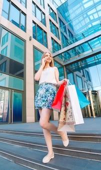 Ragazza bionda del ritratto di stile di vita giovane, con i sacchetti della spesa che esce dal negozio e che parla dal telefono cellulare.
