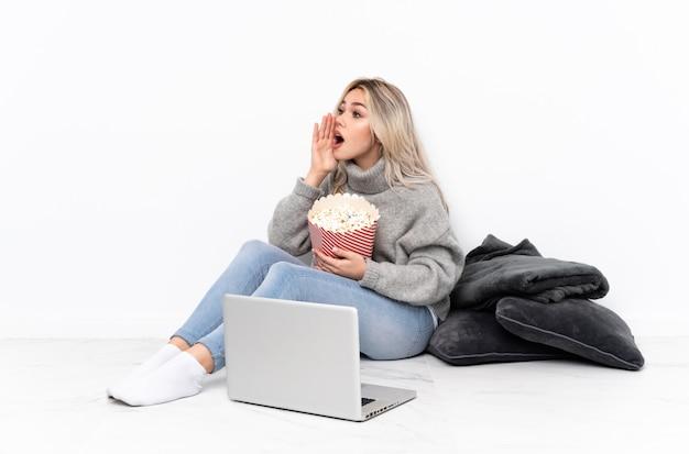 Ragazza bionda dell'adolescente che mangia popcorn mentre guardando un film sul computer portatile che grida con la bocca spalancata al laterale