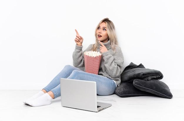 Ragazza bionda dell'adolescente che mangia popcorn mentre guardando un film sul computer portatile che indica con il dito indice una grande idea