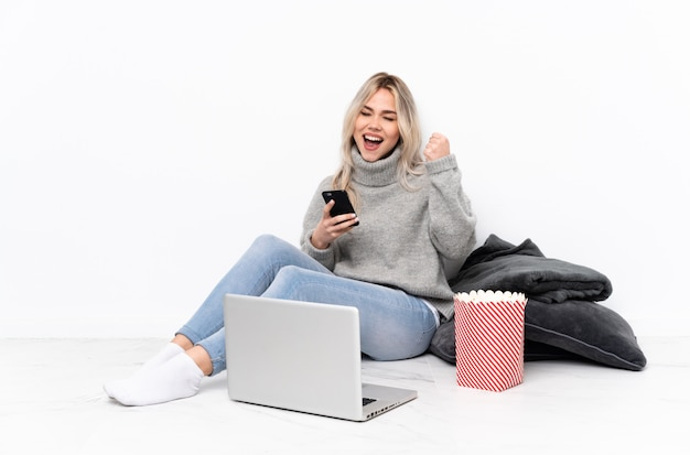 Ragazza bionda dell'adolescente che mangia popcorn mentre guardando un film sul computer portatile con il telefono nella posizione di vittoria