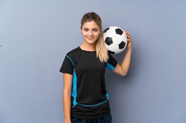 Ragazza bionda dell'adolescente del giocatore di football americano sopra la parete grigia