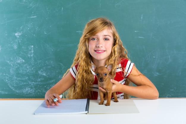 Ragazza bionda dello studente con il cucciolo di cane al bordo di classe
