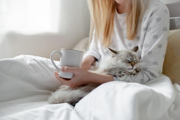 Ragazza bionda di concetto di buongiorno con il hygge della tazza di caffè e del gatto