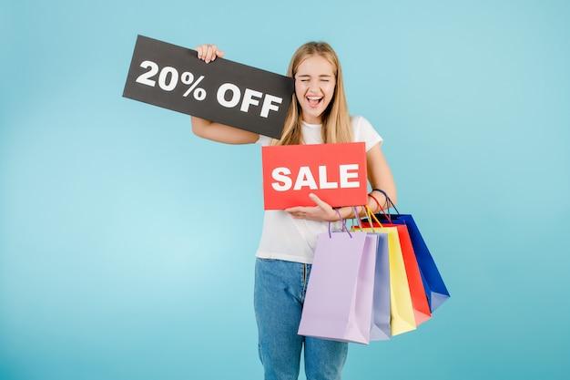 Ragazza bionda di grido felice con il 20% di sconto sul segno di vendita e sacchetti della spesa variopinti isolati sopra il blu