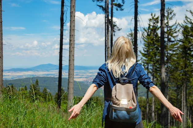 Ragazza bionda felice con packpack in montagne.