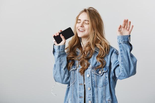 Ragazza bionda felice spensierata che gioca app karaoke sul telefono cellulare, cantando nello smartphone in auricolari