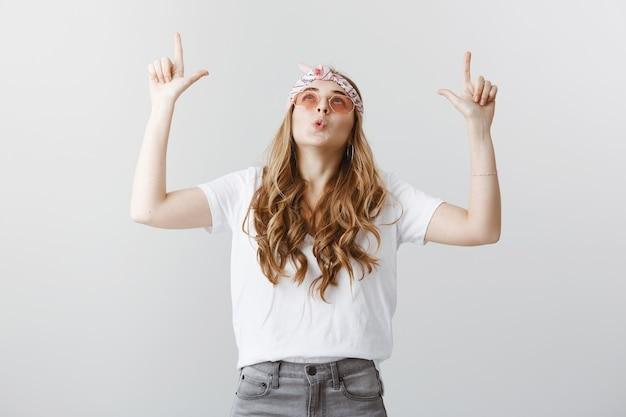 Ragazza bionda felice stupita in occhiali da sole che mostrano e puntano le dita verso l'alto