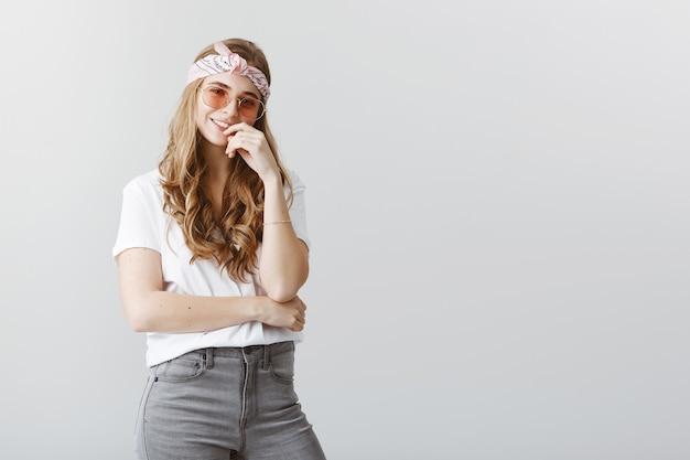 Ragazza bionda femminile alla moda in occhiali da sole che sembrano premurosi