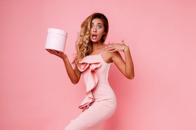 Ragazza bionda glamour con confezione regalo sorpresa viso tenendo e in piedi sul muro rosa in elegante abito rosa. emozioni estatiche.