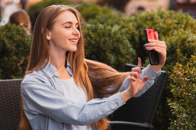 Ragazza bionda graziosa che prende i selfie