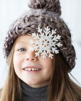 Ragazza bionda graziosa con il fiocco di neve sui suoi occhi