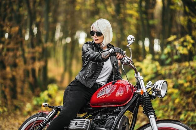 Ragazza bionda graziosa del motociclista in occhiali da sole con il motociclo rosso sulla strada nella foresta