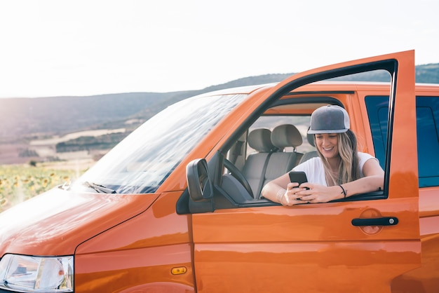Ragazza bionda graziosa e attraente con il telefono da portare della protezione in furgone arancione con le montagne