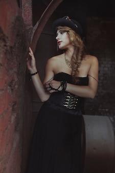Ragazza bionda in abito nero in una vecchia fabbrica abbandonata. steampunk