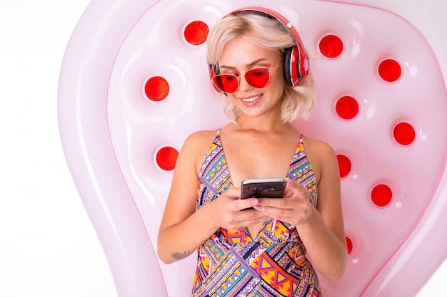 Ragazza bionda in costume da bagno e occhiali da sole con un telefono in mano su un materasso da nuoto ascolta musica in cuffia