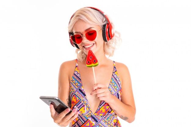 Ragazza bionda in costume da bagno e occhiali da sole con una lecca-lecca e un telefono in mano su un materasso da nuoto
