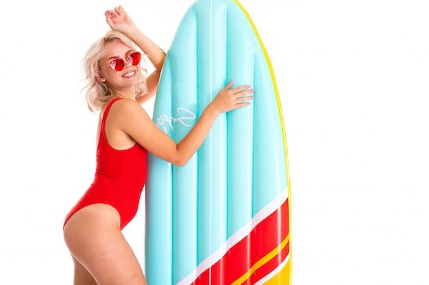 Ragazza bionda in costume da bagno rosso e occhiali da sole con un materasso da nuoto
