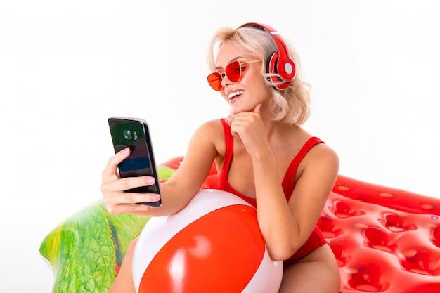 Ragazza bionda in costume da bagno rosso e occhiali da sole seduto sul materasso di nuoto e ascoltando musica in cuffia e con in mano uno smartphone