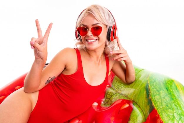 Ragazza bionda in costume da bagno rosso e occhiali da sole si trova sul materasso nuoto e ascolta la musica in cuffia