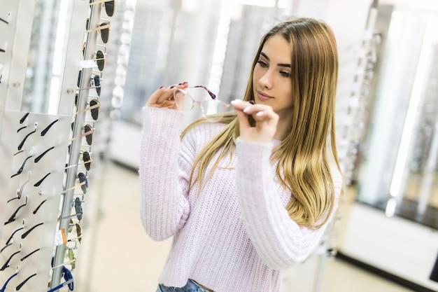 Ragazza bionda in maglione bianco sceglie nuovi occhiali medicali in negozio professionale