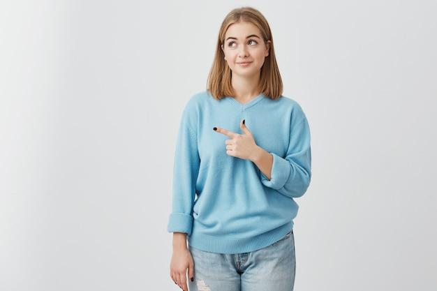 Ragazza bionda in maglione blu che guarda con i suoi occhi scuri da parte che indica con il dito indice lo spazio della copia che fa pubblicità a qualcosa. donna che posa contro la parete grigia con lo spazio della copia per testo o promozione